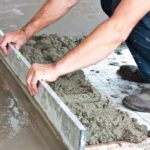 worker-knelt-down-working-with-cement